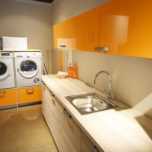 Immagine di una lavanderia minimal con ante lisce, ante arancioni, top in laminato e lavatrice e asciugatrice a colonna