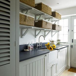 Inspiration för lantliga tvättstugor, med en rustik diskho, skåp i shakerstil, granitbänkskiva, travertin golv och tvättmaskin och torktumlare byggt in i ett skåp