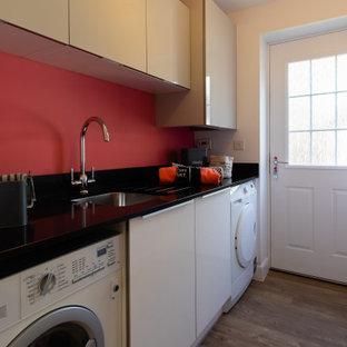 Inredning av en modern liten svarta parallell svart liten tvättstuga med garderob, med en integrerad diskho, luckor med glaspanel, grå skåp, bänkskiva i kvartsit, rosa väggar, ljust trägolv och beiget golv