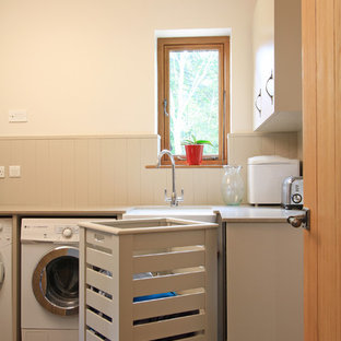Design ideas for a large contemporary l-shaped utility room in Hampshire with a submerged sink, flat-panel cabinets, beige cabinets, engineered stone countertops, white walls, porcelain flooring and a side by side washer and dryer.