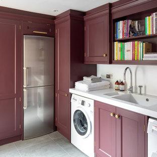 Ispirazione per una lavanderia multiuso classica di medie dimensioni con lavello integrato, ante con riquadro incassato, ante rosse, pareti bianche, lavatrice e asciugatrice affiancate, pavimento grigio e top bianco