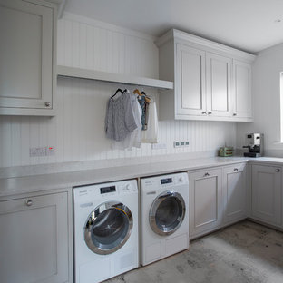 Inspiration for a large contemporary l-shaped utility room in Other with a single-bowl sink, recessed-panel cabinets, grey cabinets, white walls and a side by side washer and dryer.