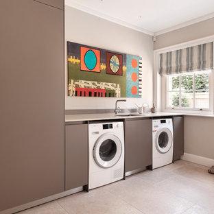Immagine di una sala lavanderia scandinava con lavello sottopiano, ante lisce, ante grigie, pareti grigie, lavatrice e asciugatrice affiancate, pavimento beige e top bianco