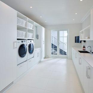 Modern inredning av ett parallellt grovkök, med en enkel diskho, vita väggar, klinkergolv i keramik, en tvättmaskin och torktumlare bredvid varandra, släta luckor, vita skåp och bänkskiva i koppar
