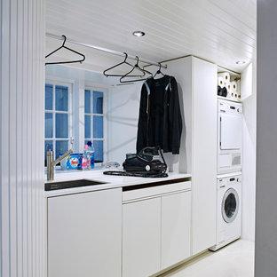Esempio di una lavanderia multiuso stile marinaro di medie dimensioni con ante lisce, ante bianche, top in superficie solida, lavatrice e asciugatrice a colonna, pareti bianche, pavimento in gres porcellanato e lavello sottopiano