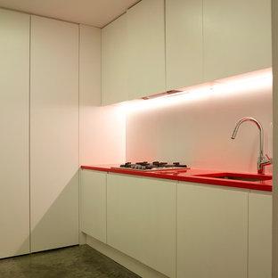 Inredning av en modern mellanstor röda l-formad rött liten tvättstuga, med en nedsänkt diskho, släta luckor, vita skåp, bänkskiva i koppar, vita väggar, betonggolv, en tvättpelare och grått golv