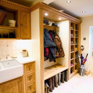 Inspiration för klassiska tvättstugor, med en rustik diskho, skåp i shakerstil, skåp i mellenmörkt trä, vita väggar och kalkstensgolv