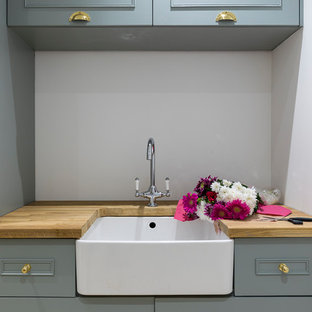 Medium sized farmhouse single-wall utility room in London with a belfast sink, shaker cabinets, blue cabinets, wood worktops, grey walls, porcelain flooring and a concealed washer and dryer.