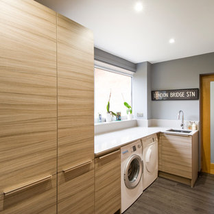 Example of a mid-sized trendy l-shaped laminate floor and gray floor utility room design in West Midlands with a single-bowl sink, gray walls, white countertops and light wood cabinets