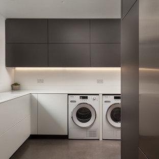 Modern inredning av ett vit l-format vitt grovkök, med en integrerad diskho, släta luckor, grå skåp, vita väggar, betonggolv, en tvättmaskin och torktumlare bredvid varandra och grått golv