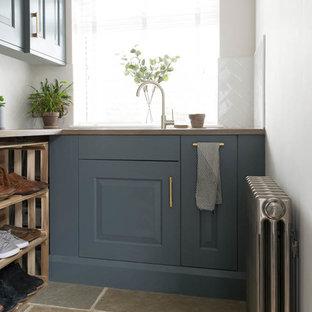 Immagine di una piccola lavanderia rustica con ante blu, top in legno, pavimento in pietra calcarea, pavimento grigio e top marrone