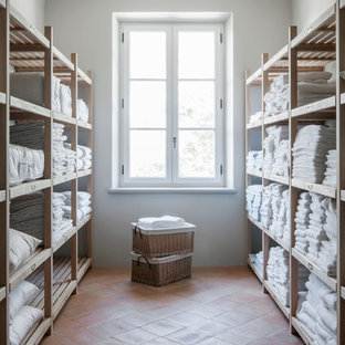 Large farmhouse galley separated utility room in London with open cabinets, light wood cabinets, white walls and ceramic flooring.
