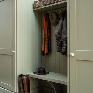 Photo of a mid-sized contemporary single-wall laundry cupboard in London with shaker cabinets, green cabinets and red floor.