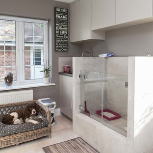 This is an example of a small classic single-wall utility room in Hampshire with flat-panel cabinets, white cabinets, grey walls and beige floors.