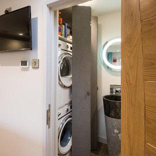 Foto på ett litet funkis linjärt grovkök, med släta luckor, grå skåp, vita väggar, vinylgolv och en tvättpelare