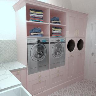 Cette image montre une petit buanderie style shabby chic en L multi-usage avec un évier de ferme, un placard à porte affleurante, des portes de placard en bois clair, un plan de travail en quartz, une crédence rose, une crédence en carreau de céramique, un mur blanc, un sol en carrelage de céramique, des machines superposées, un sol rose, un plan de travail blanc et un plafond à caissons.