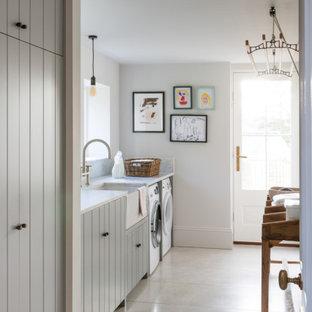 Bild på ett stort vintage vit linjärt vitt grovkök, med en rustik diskho, luckor med lamellpanel, grå skåp, vita väggar, klinkergolv i porslin, en tvättmaskin och torktumlare bredvid varandra och grått golv
