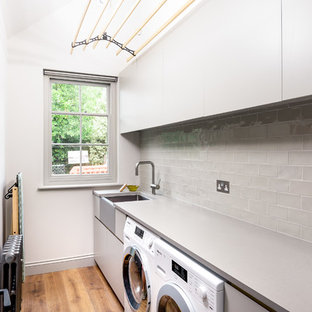 This is an example of a small contemporary single-wall separated utility room in Sussex with a belfast sink, flat-panel cabinets, grey cabinets, granite worktops, white walls, a side by side washer and dryer, grey worktops, medium hardwood flooring and brown floors.