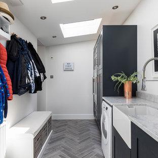 Cette photo montre une buanderie tendance dédiée et de taille moyenne avec un évier de ferme, un placard avec porte à panneau encastré, un plan de travail en marbre, un sol gris et des portes de placard noires.