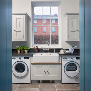 This is an example of a mid-sized transitional laundry room in Hampshire with grey cabinets, granite benchtops, black splashback, limestone floors, shaker cabinets and a farmhouse sink.