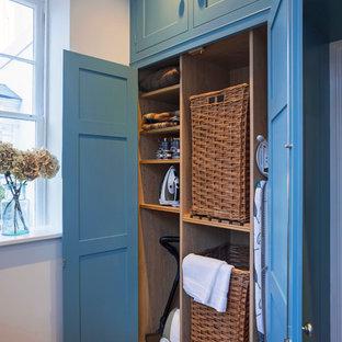 Exempel på en mellanstor klassisk tvättstuga, med blå skåp, kalkstensgolv och skåp i shakerstil