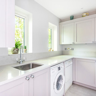Design ideas for a traditional l-shaped utility room in Berkshire with a submerged sink, shaker cabinets, grey cabinets, white walls, a side by side washer and dryer, beige floors and white worktops.