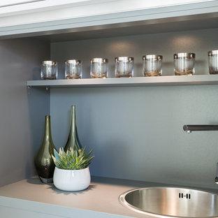 Inredning av en modern liten grå linjär grått liten tvättstuga, med en enkel diskho, släta luckor, grå skåp, laminatbänkskiva, beige väggar, heltäckningsmatta och grått golv
