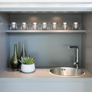 Foto på en liten funkis grå linjär liten tvättstuga, med en enkel diskho, släta luckor, grå skåp, laminatbänkskiva, beige väggar, heltäckningsmatta och grått golv