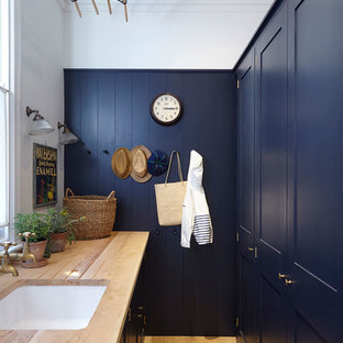 This is an example of a small traditional galley separated utility room in London with recessed-panel cabinets, blue cabinets, wood worktops, light hardwood flooring, beige floors and beige worktops.