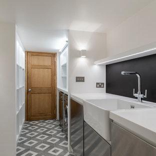 Inredning av ett klassiskt parallellt grovkök, med en rustik diskho, släta luckor, skåp i rostfritt stål, bänkskiva i koppar, vita väggar, klinkergolv i porslin, en tvättmaskin och torktumlare bredvid varandra och grått golv