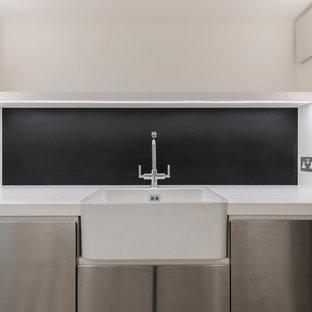 Esempio di una lavanderia multiuso classica con lavello stile country, ante lisce, ante in acciaio inossidabile, top in superficie solida, pareti bianche, pavimento in gres porcellanato, lavatrice e asciugatrice affiancate e pavimento grigio