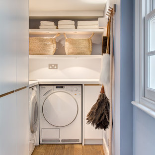 Inspiration for a contemporary l-shaped utility room in London with flat-panel cabinets, white walls, medium hardwood flooring, a side by side washer and dryer and white cabinets.