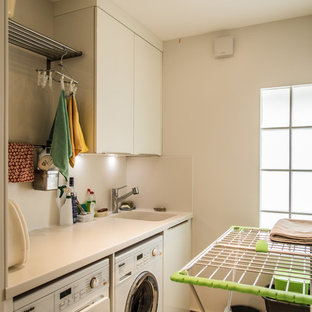 Design ideas for a modern galley separated utility room in London with an integrated sink, flat-panel cabinets, white cabinets, engineered stone countertops, white walls, ceramic flooring and a side by side washer and dryer.