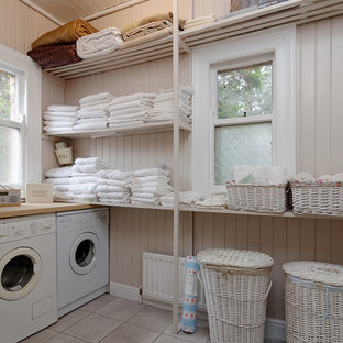 Photo of a traditional separated utility room in Belfast with open cabinets, beige walls, a side by side washer and dryer and grey floors.