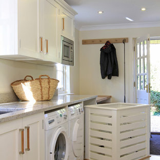 Example of a classic laundry room design in Hampshire with white cabinets