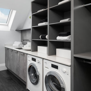 Photo of a large contemporary single-wall dedicated laundry room in Buckinghamshire with an undermount sink, open cabinets, grey cabinets, white walls, dark hardwood floors, a side-by-side washer and dryer and white benchtop.