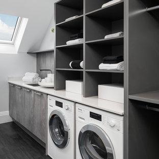 Inspiration för en stor funkis vita linjär vitt tvättstuga enbart för tvätt, med en undermonterad diskho, öppna hyllor, grå skåp, vita väggar, mörkt trägolv och en tvättmaskin och torktumlare bredvid varandra