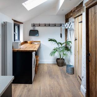Immagine di una piccola sala lavanderia country con top in legno, pareti bianche, parquet chiaro, pavimento beige e top beige