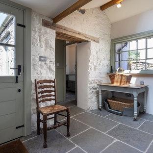 Inspiration för stora klassiska parallella grått tvättstugor enbart för tvätt, med en rustik diskho, skåp i shakerstil, gröna skåp, granitbänkskiva, vita väggar, skiffergolv, tvättmaskin och torktumlare byggt in i ett skåp och blått golv