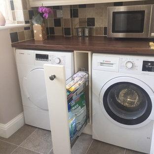 Immagine di una piccola lavanderia country con ante con bugna sagomata, ante beige, top in legno, pareti beige, pavimento con piastrelle in ceramica, lavatrice e asciugatrice affiancate e top marrone