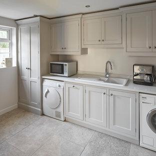 Exempel på ett stort klassiskt linjärt grovkök, med grå skåp, bänkskiva i kvarts, beige stänkskydd, stänkskydd i sten, kalkstensgolv, en nedsänkt diskho, luckor med profilerade fronter och vita väggar