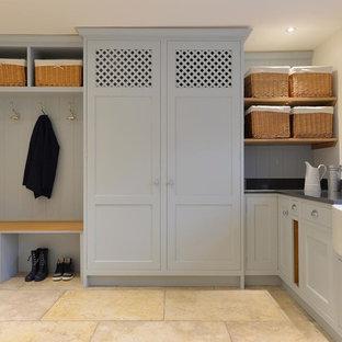 Immagine di una grande lavanderia classica con lavello stile country, pavimento in pietra calcarea, ante in stile shaker, ante grigie, pareti bianche, lavatrice e asciugatrice nascoste e top grigio