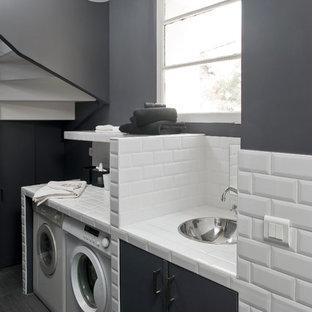 Modern inredning av en mellanstor linjär tvättstuga enbart för tvätt, med grå väggar, en tvättmaskin och torktumlare bredvid varandra, kaklad bänkskiva, en undermonterad diskho och målat trägolv