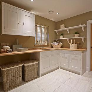 Réalisation d'une buanderie champêtre en L multi-usage avec un évier encastré, un placard à porte shaker, des portes de placard blanches, un plan de travail en bois, un mur beige, un sol gris et un plan de travail beige.