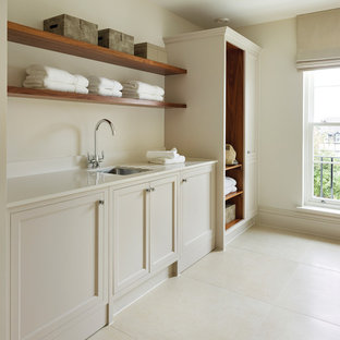 Photo of a traditional separated utility room in Other with a submerged sink, recessed-panel cabinets, beige cabinets, beige walls, beige floors and white worktops.