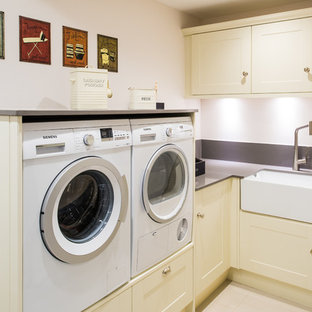 This is an example of a small transitional l-shaped utility room in West Midlands with a drop-in sink, flat-panel cabinets, beige cabinets, white walls, a side-by-side washer and dryer and grey benchtop.