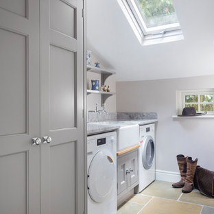 Inspiration for a small transitional single-wall dedicated laundry room in Hampshire with a farmhouse sink, granite benchtops, a side-by-side washer and dryer, recessed-panel cabinets, grey cabinets, grey walls, travertine floors and grey benchtop.