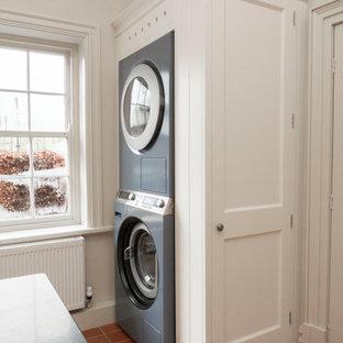 Immagine di una lavanderia multiuso classica di medie dimensioni con lavello stile country, ante con riquadro incassato, ante bianche, top in granito, pareti beige, pavimento in terracotta, lavatrice e asciugatrice a colonna, pavimento arancione e top nero