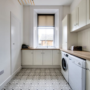 Large classic l-shaped separated utility room in Glasgow with an integrated sink, shaker cabinets, beige cabinets, wood worktops, beige walls, a side by side washer and dryer, multi-coloured floors and brown worktops.