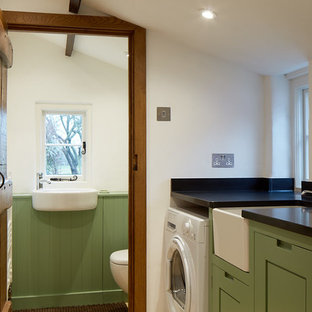 Design ideas for a classic single-wall utility room in Other with a belfast sink, shaker cabinets, green cabinets, white walls and black worktops.